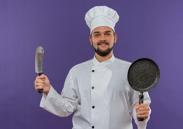 Lächelnder junger männlicher koch in der kochuniform, die hackbeil und bratpfanne lokalisiert auf lila raum hält