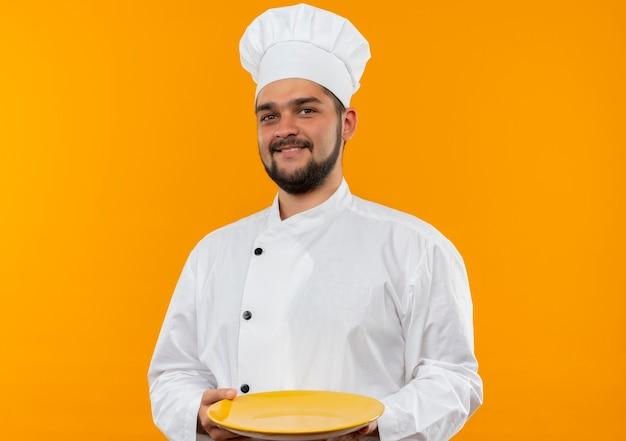 Lächelnder junger männlicher koch in der kochuniform, die leere platte lokalisiert auf orange raum hält