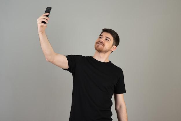 Lächelnder junger mann auf einem grau, das ein selfie macht.