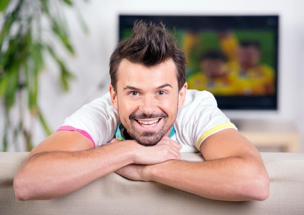 Lächelnder junger mann beim aufpassen des spiels.