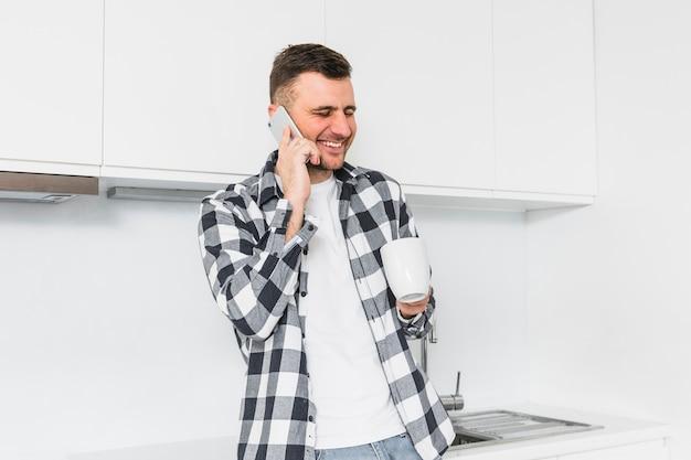 Lächelnder junger mann, der am handy in der hand hält weiße schale spricht