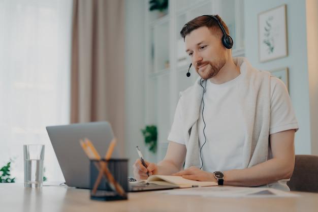 Lächelnder junger mann, der am tisch sitzt und ein headset verwendet, während er auf den laptop-bildschirm schaut und notizen im notebook macht, männlicher freiberufler in kopfhörern, der online-meetings mit kollegen hat. freiberufliches konzept