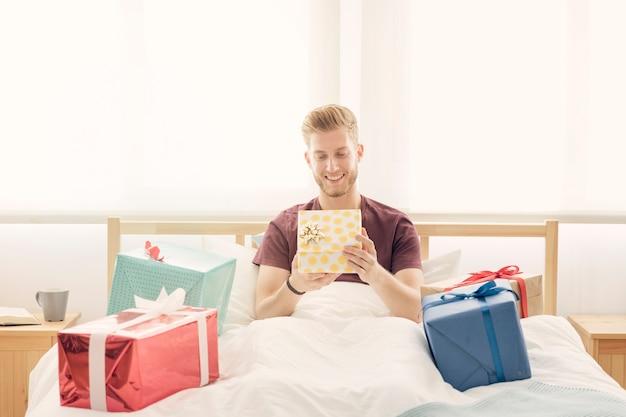 Lächelnder junger mann, der auf dem bett umgeben mit bunten geschenken sitzt