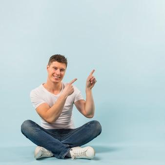 Lächelnder junger mann, der auf dem boden zeigt seine finger oben gegen blauen hintergrund sitzt