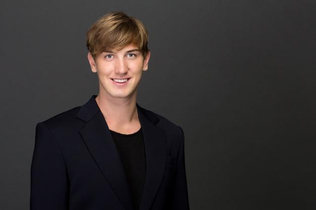 Lächelnder junger mann, der blazer trägt