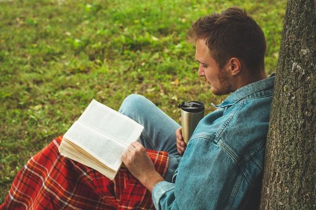 Lächelnder junger mann, der buch draußen mit einem warmen roten plaid und einer tasse tee liest. herbstferien und lifestyle-konzept.