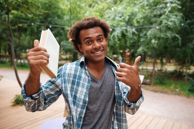 Lächelnder junger mann, der buch hält und daumen oben zeigt