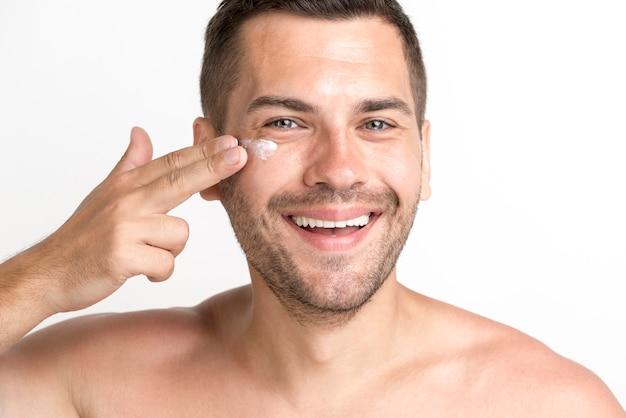 Lächelnder junger mann, der creme auf gesicht aufträgt und kamera betrachtet