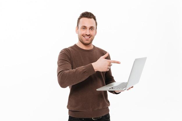 Lächelnder junger mann, der das computerzeigen verwendet.