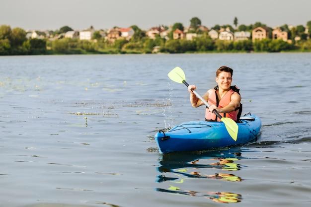 Lächelnder junger mann, der das kayak fahren genießt