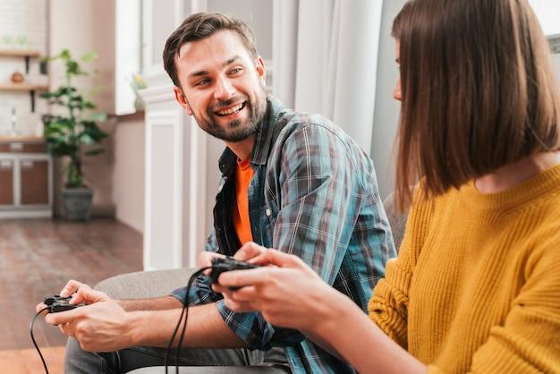Lächelnder junger mann, der das videospiel mit ihrer frau spielt