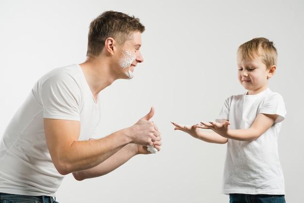 Lächelnder junger mann, der daumen herauf zeichen zu seinem sohn zeigt, der unordentliche hand mit schaum zeigt