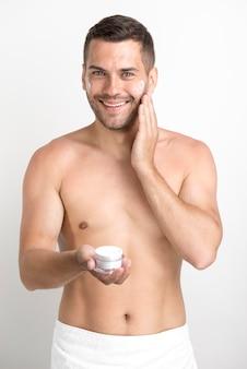 Lächelnder junger mann, der die gesichtscreme betrachtet die kamera steht gegen weißen hintergrund aufträgt