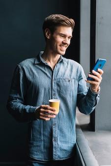 Lächelnder junger mann, der die mitnehmerkaffeetasse betrachtet mobiltelefon betrachtet