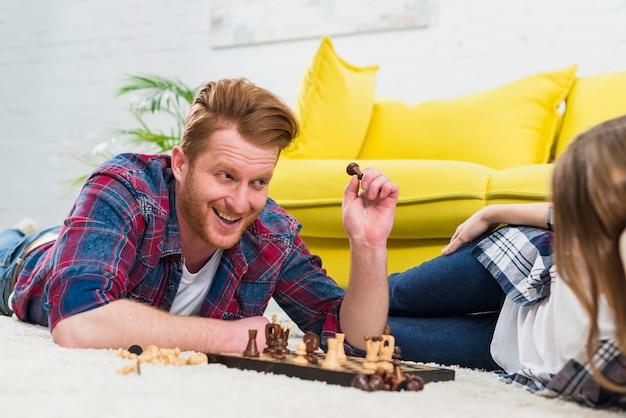 Lächelnder junger mann, der die schachfigur betrachtet ihre freundin liegt auf teppich hält