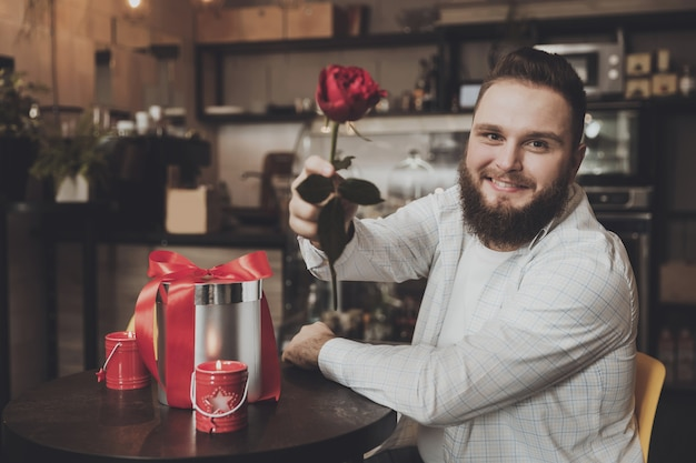 Lächelnder junger mann, der die tabelle hält eine rose sitzt