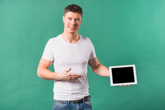 Lächelnder junger mann, der digitale tablette gegen grünen hintergrund zeigt
