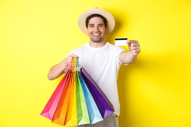 Lächelnder junger mann, der dinge mit kreditkarte kauft, einkaufstaschen hält und glücklich schaut, über gelbem hintergrund stehend.
