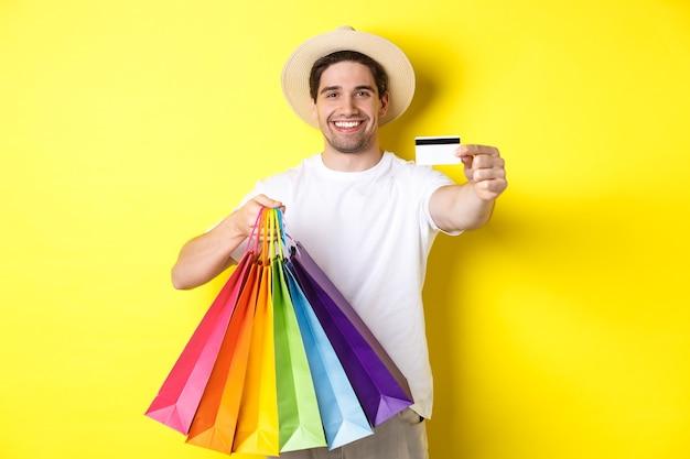Lächelnder junger mann, der dinge mit kreditkarte kauft, einkaufstaschen hält und glücklich schaut, über gelber wand stehend