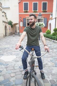 Lächelnder junger mann, der draußen auf fahrrad sitzt