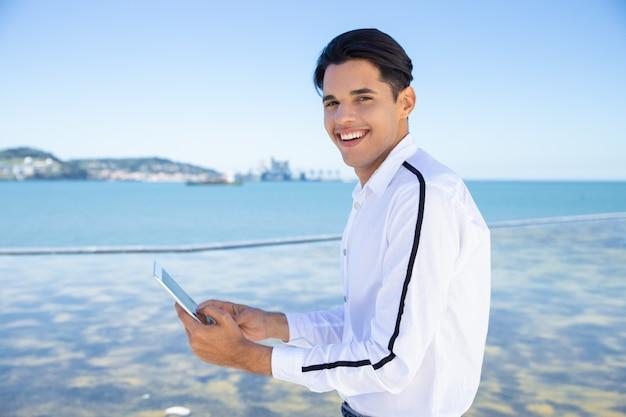 Lächelnder junger mann, der draußen tablette verwendet