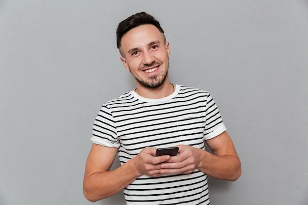 Lächelnder junger mann, der durch handy plaudert