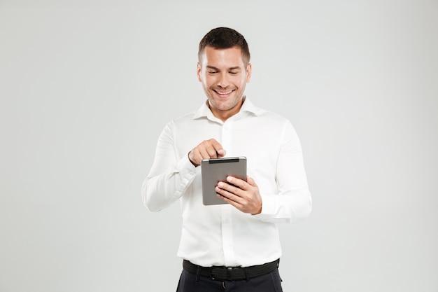 Lächelnder junger mann, der durch tablet-computer plaudert.