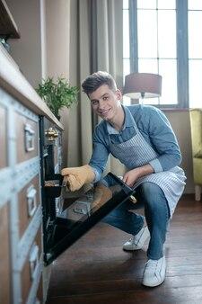 Lächelnder junger mann, der ein backblech aus dem ofen herausnimmt.