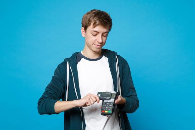 Lächelnder junger mann, der ein drahtloses modernes bankzahlungsterminal hält, um kreditkartenzahlungen einzeln auf blauer wand zu verarbeiten und zu erwerben. menschen aufrichtige emotionen, lifestyle-konzept.