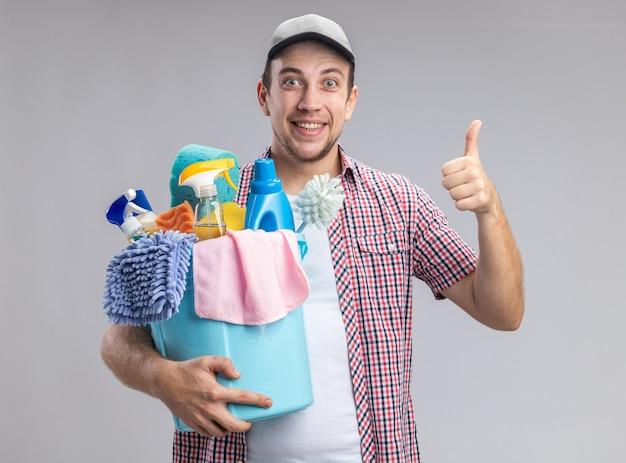 Lächelnder junger mann, der eine kappe trägt, die einen eimer mit reinigungswerkzeugen hält, der daumen nach oben zeigt, isoliert auf weißer wand