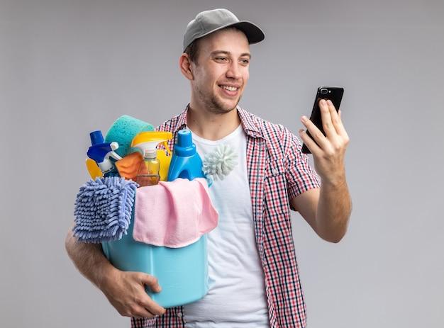 Lächelnder junger mann, der eine kappe trägt, die einen eimer mit reinigungswerkzeugen hält und das telefon in seiner hand isoliert auf weißer wand betrachtet
