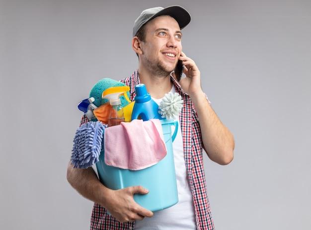 Lächelnder junger mann, der eine kappe trägt und einen eimer mit reinigungswerkzeugen hält, spricht am telefon isoliert auf weißer wand