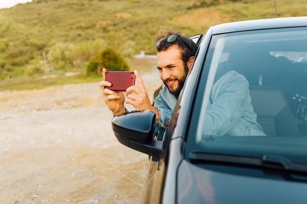 Lächelnder junger mann, der foto am telefon macht