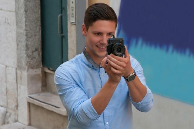 Lächelnder junger mann, der foto auf kamera in der straße macht