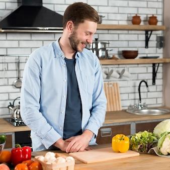 Lächelnder junger mann, der frischgemüse auf küchenarbeitsplatte betrachtet