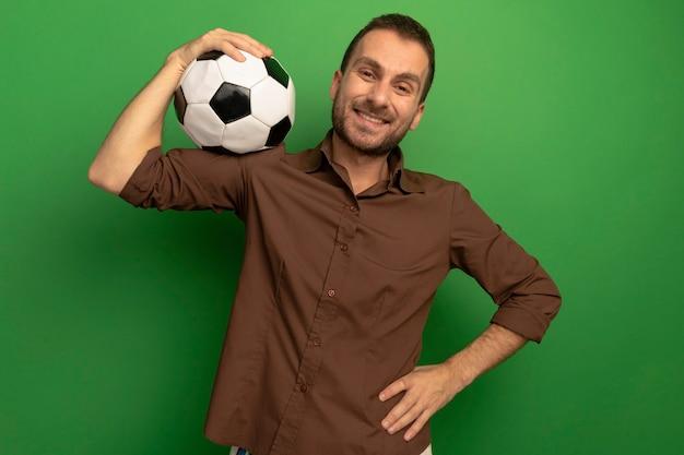 Lächelnder junger mann, der fußball auf schulter hält, die front betrachtet, die hand auf taille lokalisiert auf grüner wand hält