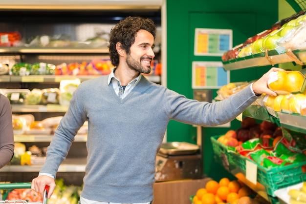 Lächelnder junger mann, der gemüse in einem gemischtwarenladen aufhebt