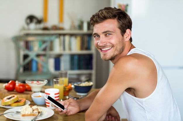 Lächelnder junger mann, der handy am frühstückstische verwendet