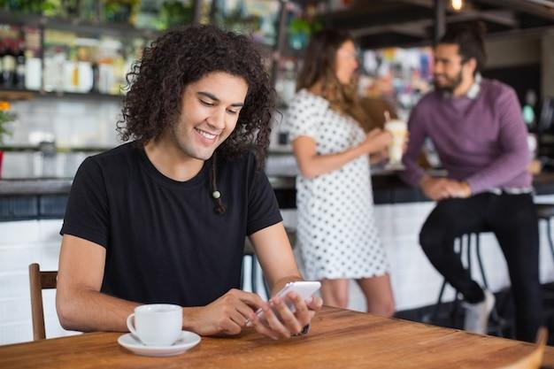 Lächelnder junger mann, der handy beim sitzen im restaurant verwendet