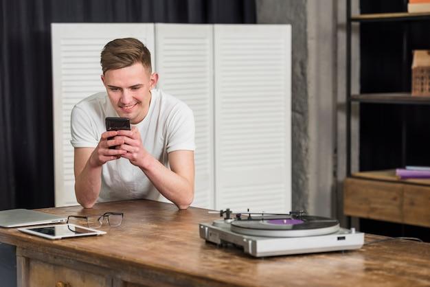 Lächelnder junger mann, der handy mit digitaler tablette verwendet; brillen und plattenspieler-schallplattenspieler auf dem tisch