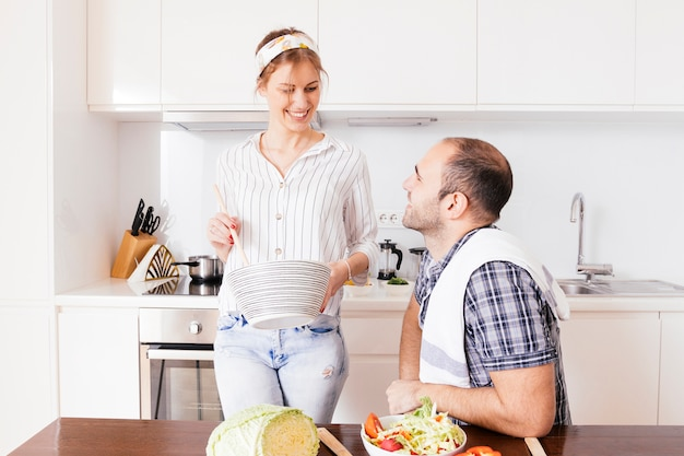 Lächelnder junger mann, der ihre frau zubereitet lebensmittel in der küche zubereitet