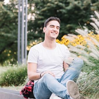 Lächelnder junger mann, der im garten sitzt