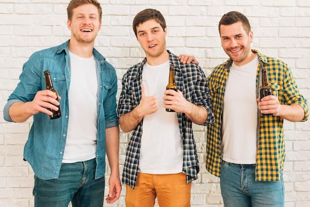 Lächelnder junger mann, der in der hand die bierflasche steht mit seinem freund zeigt daumen herauf zeichen hält