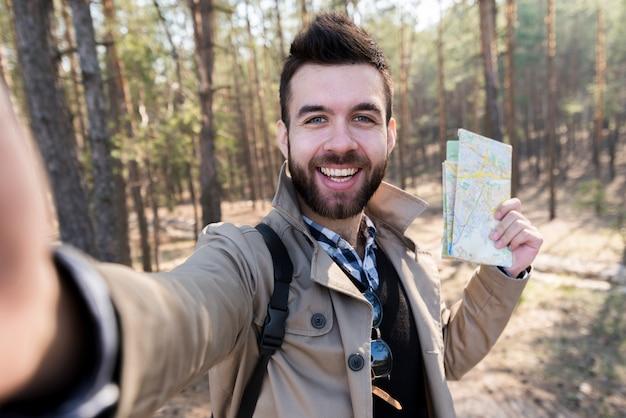 Lächelnder junger mann, der in der hand die karte nimmt selfie im wald hält