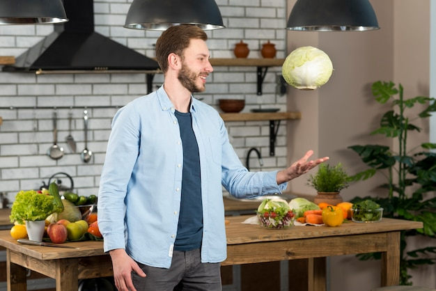 Lächelnder junger mann, der in der küche steht, ganzen kohl in einer luft zu werfen