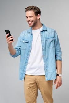 Lächelnder junger mann, der jeanshemd trägt, das selfie foto auf smartphone nimmt oder videoanruf stehend macht