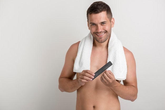 Lächelnder junger mann, der kamera beim polieren seiner nägel mit geldstrafe betrachtet