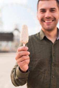 Lächelnder junger mann, der köstliche eis am stiel-eiscreme hält