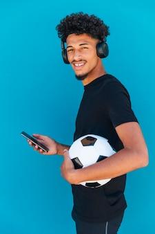 Lächelnder junger mann, der mit fußball und telefon steht