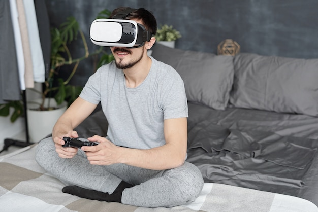 Lächelnder junger mann, der mit gekreuzten beinen auf bett sitzt und videospiel mit joystick und virtual-reality-headset spielt